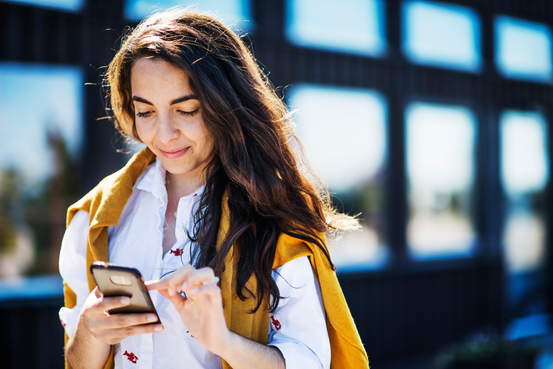 ผู้หญิงกำลังถือโทรศัพท์มือถือ